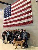 Foto de grupo en el aeropuerto con bandera de EEUU de fondo