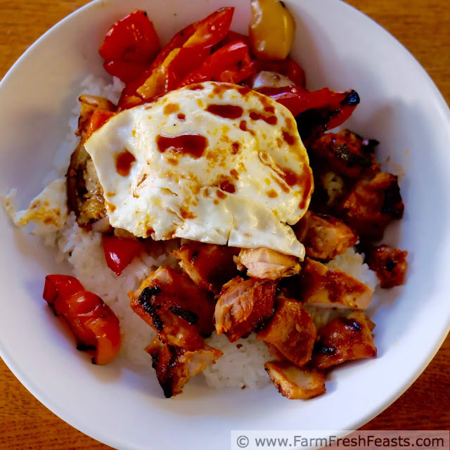 a square image of a fried egg atop grilled chicken, eggplant, and peppers over rice