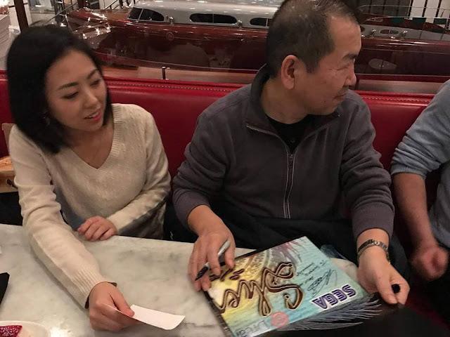 Yu Suzuki signing a poster