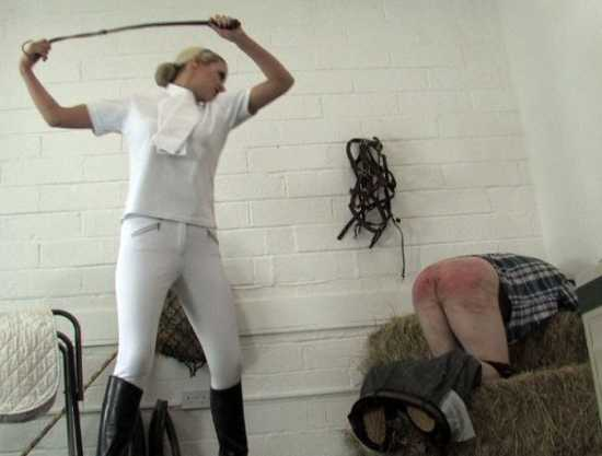 mistress in jodhpurs and boots whips red ass of a slave