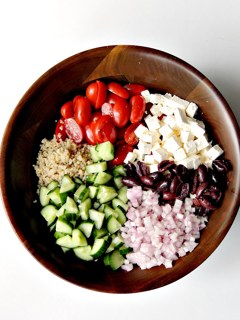 Ingredients for Mediterranean Quinoa Salad in a wooden salad bowl on a white background.