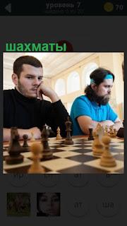 за столом сидят люди и играют в шахматы