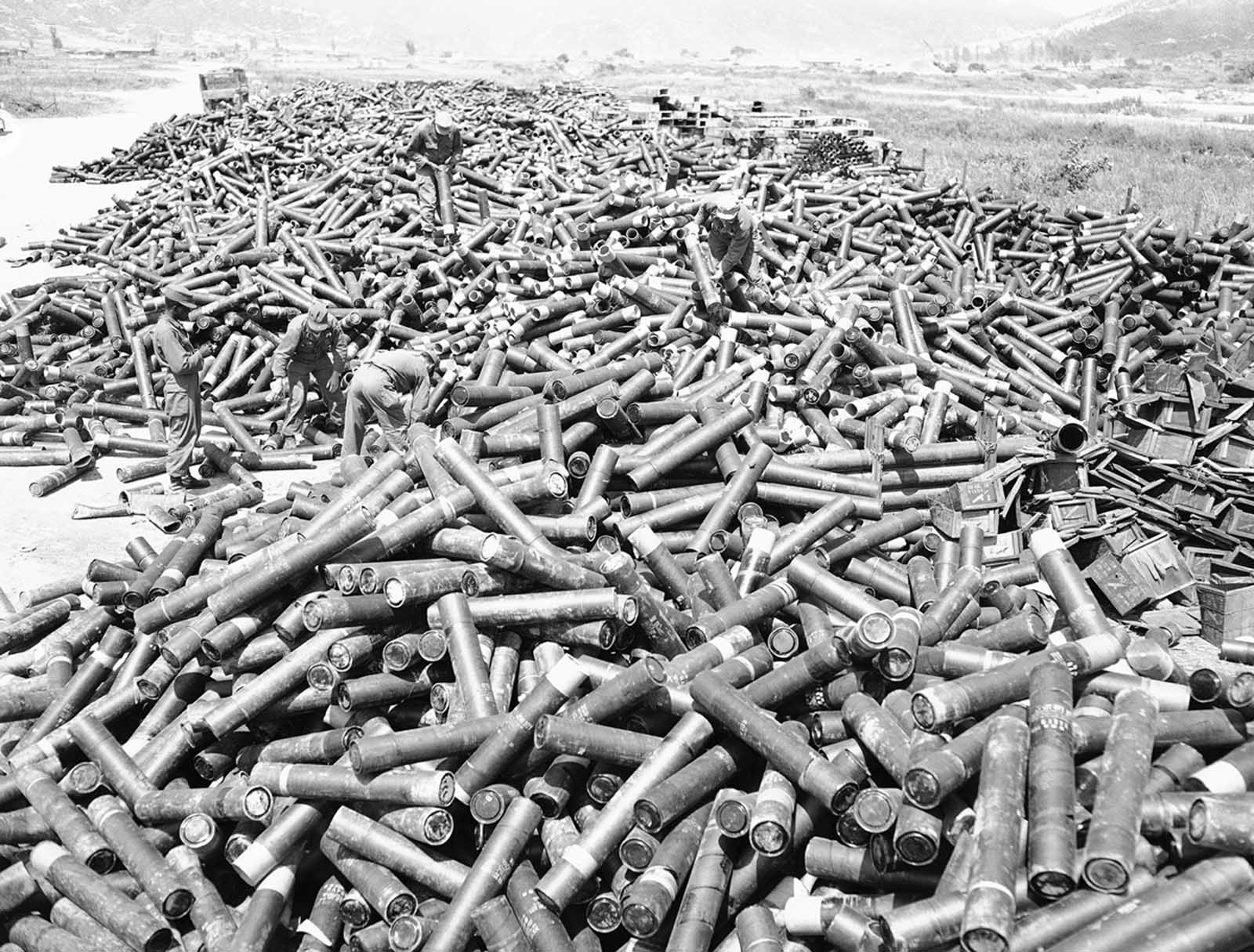 GIs and Korean service corpsmen stack up an enormous pile of empty artillery and mortar shell casings at a collecting point near the front, pointing to the huge amount of lead thrown at the enemy in four days of fighting for outpost Harry, on June 18, 1953.