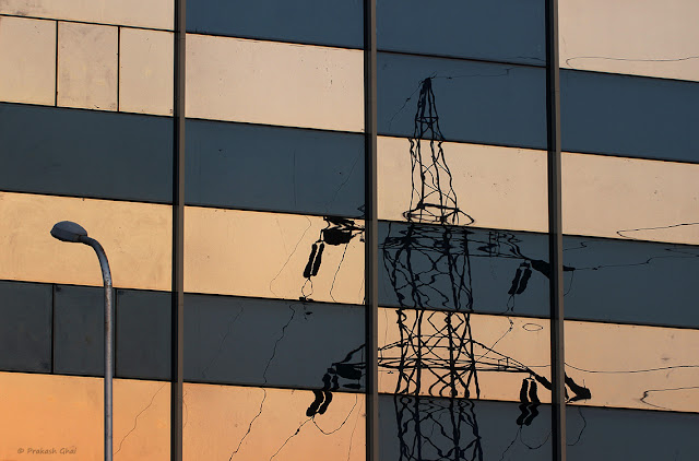 Reflection of Electricity Tower on Glass Building used as a Minimalist Photography Subject