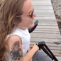 Sarah sidder på stranden i sin elkørestol, iklædt orange solbriler og viltert hår. Hendes arme er bare og den ene er dækket af en tatovering af superheltinden Oracle.
