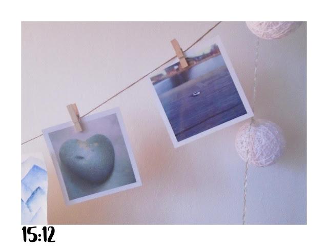 zdjęcia przywieszone na sznurku za pomocą drewnianych klamerek.