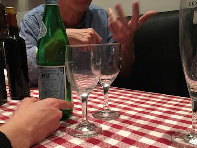 Sprechende Hände, kariertes Tischtuch, Gläser, Flaschen