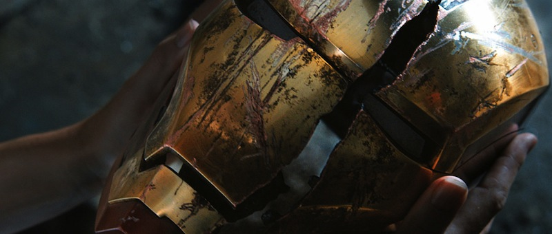 A scarred, cracked Iron Man helmet in close-up held by Tony Stark
