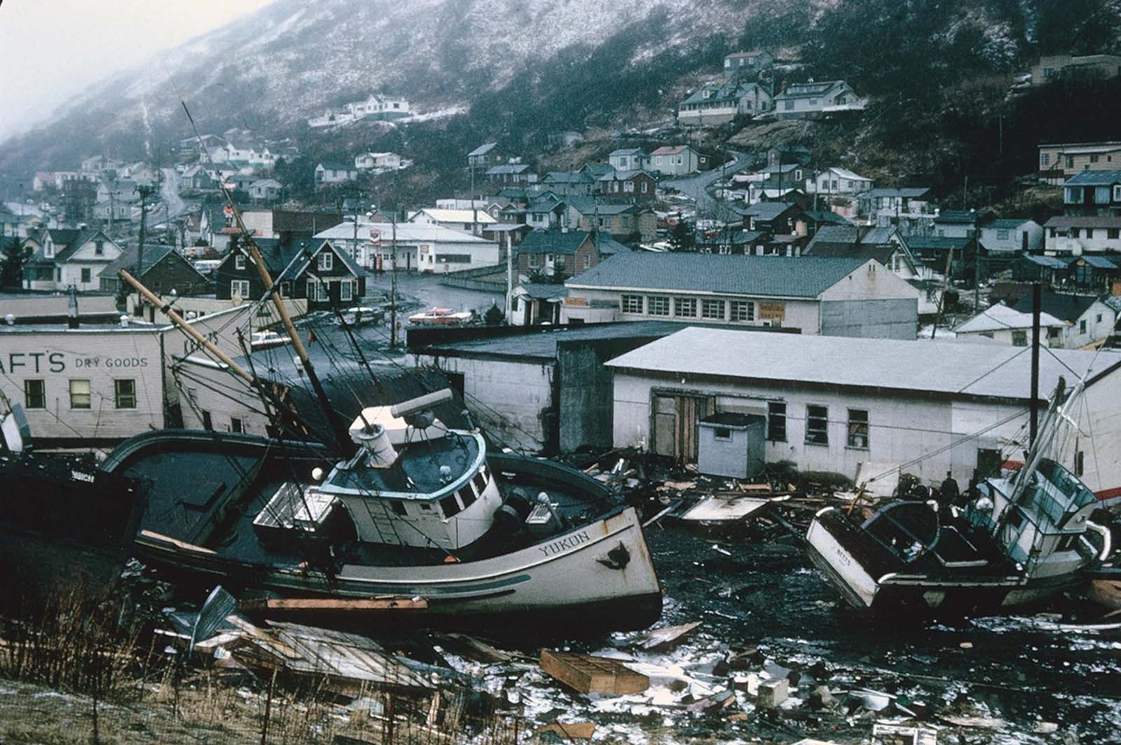 Chaotic condition of the commercial section of Kodiak following inundation by seismic sea waves. The small boat harbor contained an estimated 160 crab and salmon fishing boats when the waves struck.