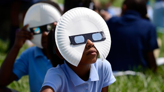 Một học sinh sử dụng kính quan sát Mặt Trời để tận mắt theo dõi nhật thực. Hình ảnh: Jeff Curry/Getty Images.