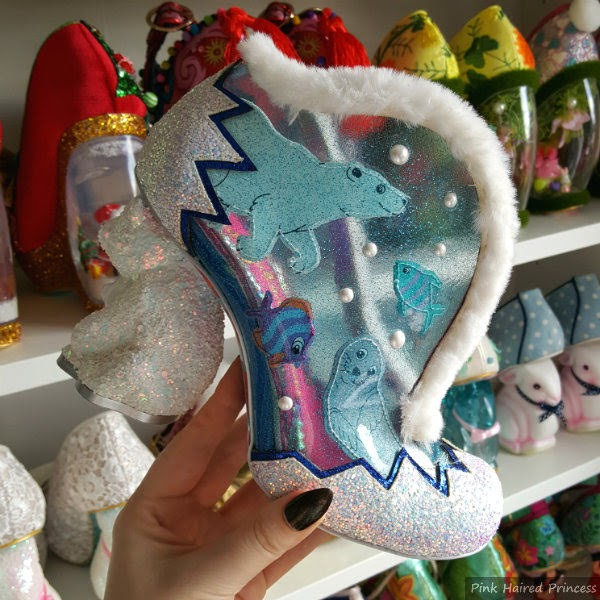 polar bear heeled shoe in hand in front of shoe shelves