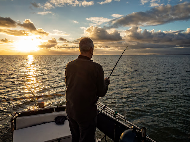 Photo of Phil fishing from Ravensdale's aft deck as the sun goes down