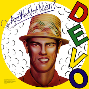 "Portada del LP de DEVO: Q: Are We Not Men? We Are Devo! de agosto de 1978. La portada la cara de un hombre con sombrero inscrito en un círculo; el resto de la carátula es amarilla, el título del álbum ""manuscrito"" arriba y a la derecha las letras DEVO en varios colores (D, rojo, E, verde, V, amarilla, O, violeta)"