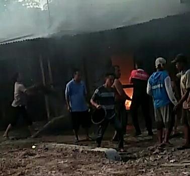 Warga dan petugas pemadam kebakaran berusaha memadamkan api.