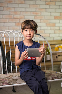 a child wearing earphones holds a tablet