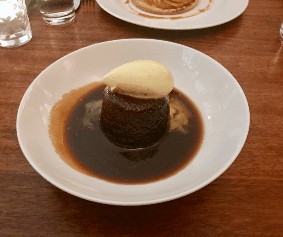 sticky toffee pudding topped with clotted cream, surrounded by toffee sauce, sitting in a white bowl