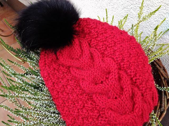 Czerwona czapka w warkocze z czarnym pomponem