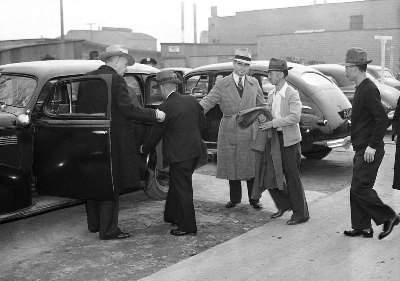 Two plainclothes men, left, watch as Japanese aliens are removed from their homes on Terminal Island, a vital Naval and Shipbuilding center in Los Angeles, California, on February 3, 1942. Some 400 male Japanese aliens -- Terminal Island residents -- were rounded up early on February 2 by 180 federal, city and county officers.