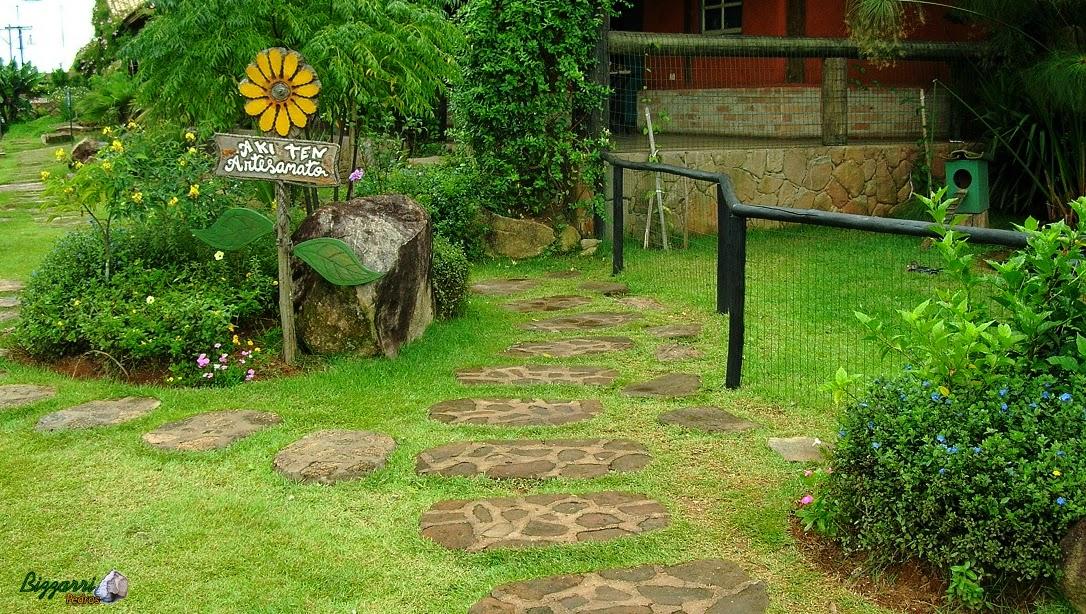 Caminhos no jardim com pedras moledo com tamanhos variados assentado na massa de cimento.