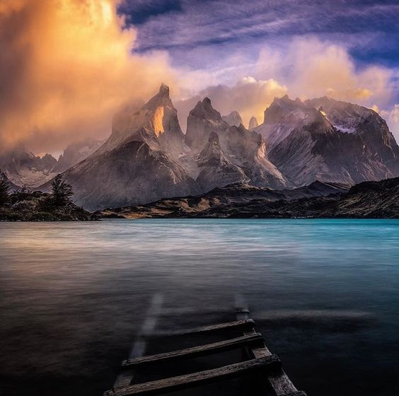 Picture of mountains on Lake Pehoe, Chile, with a ladder or bridge submerged in the water.