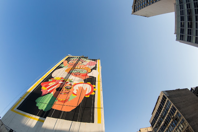 Há dez dias, a rua Sapucaí foi transformada por grafites e pinturas. Na semana passada, do charmoso mirante em frente à Benfeitoria, no bairro Floresta, era possível ver cinco artistas suspensos em andaimes, espalhando os últimos lances de tinta spray pelos ares e finalizando gigantescas pinturas de até 50 metros de altura, em quatros prédios do hipercentro de Belo Horizonte. No fim do dia, exaustos do trabalho intenso, eles observavam as próprias obras quase acabadas: uma baita provocação à cidade.