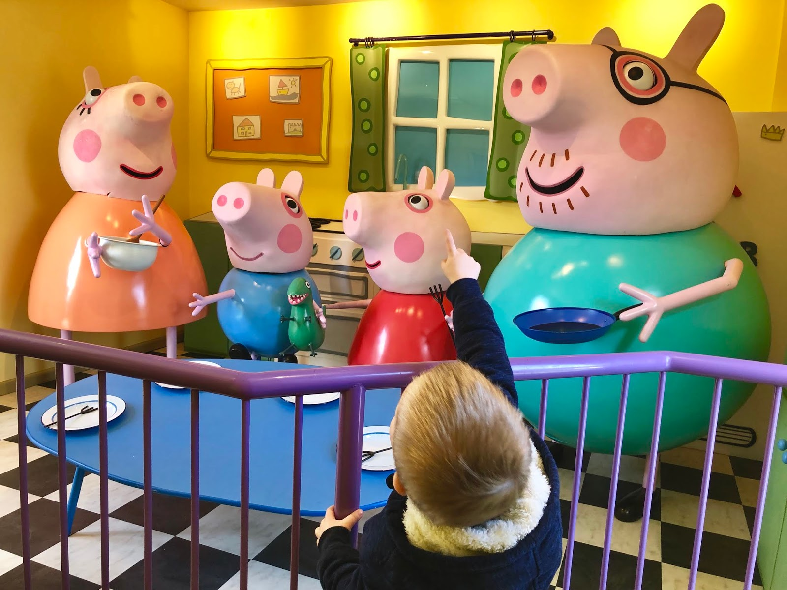 young boy pointing at large peppa pig family statues at peppa pig world paultons park