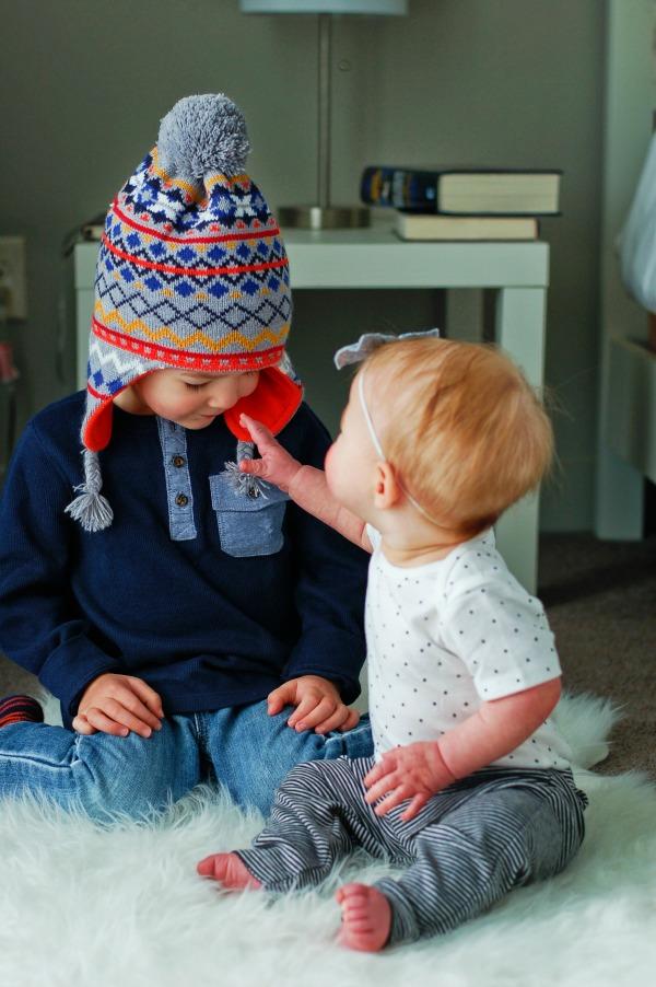 Two children interacting on floor in baby registry clothing.
