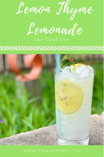 A glass of lemonade, with lemon slices and a lot of ice and a sprig of thyme in the glass sitting on a rock wall.