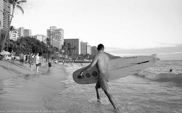 black and white film photo of a surfer leaving the ocean in Waikiki