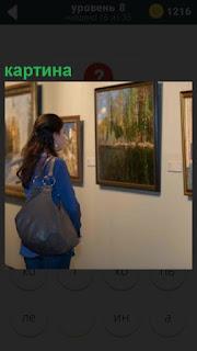 В музее на стене рассматривает картину очередной посетитель женщина