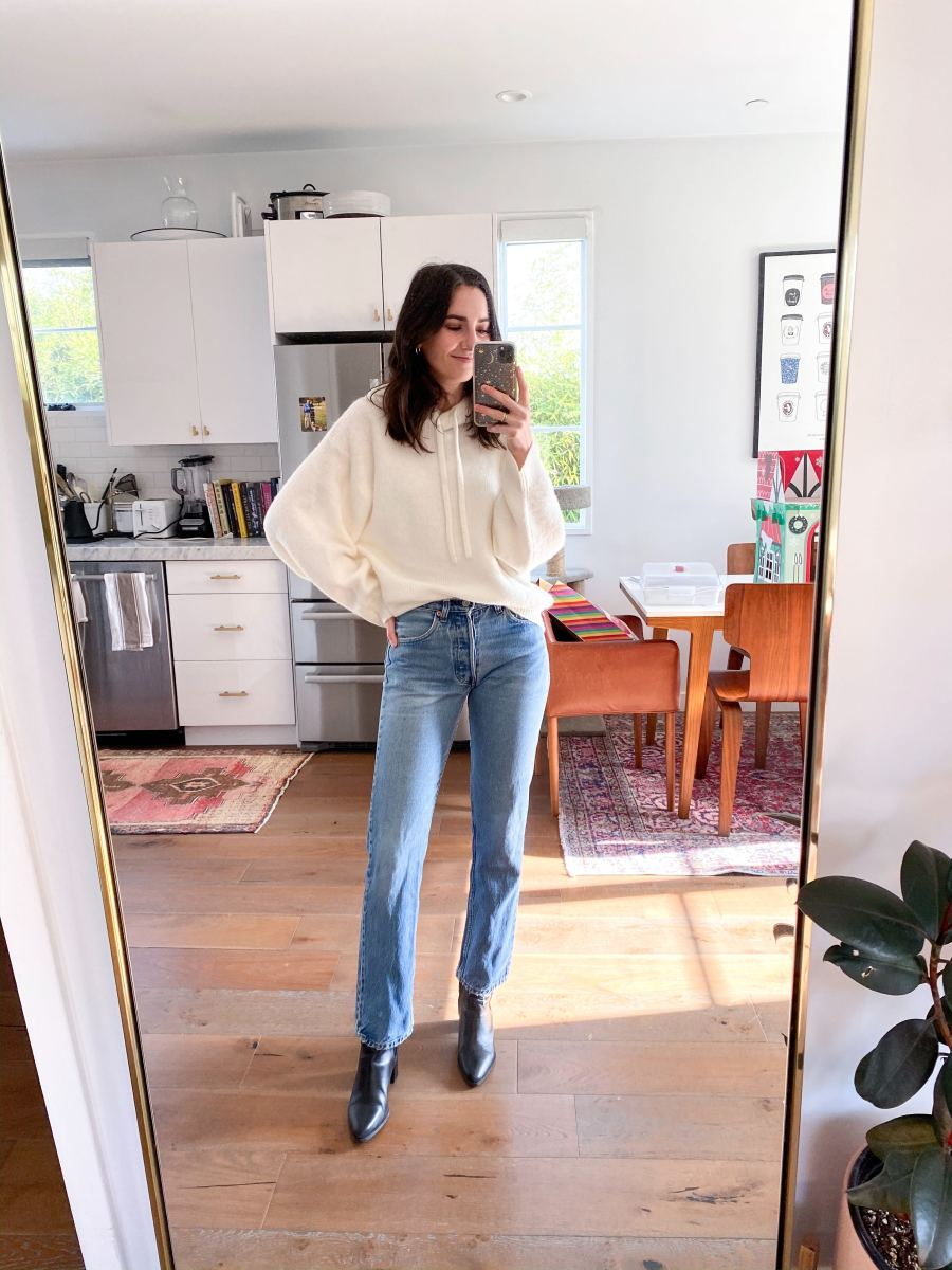 A Stylish Way to Wear a Hoodie for Spring  — Cupcakes and Cashmere team member in a white hooded sweatshirt, Levi's jeans, and black ankle boots