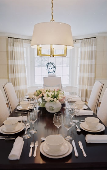 Formal dining room with dark wood table, upholstered white chairs and striped beige and white curtains