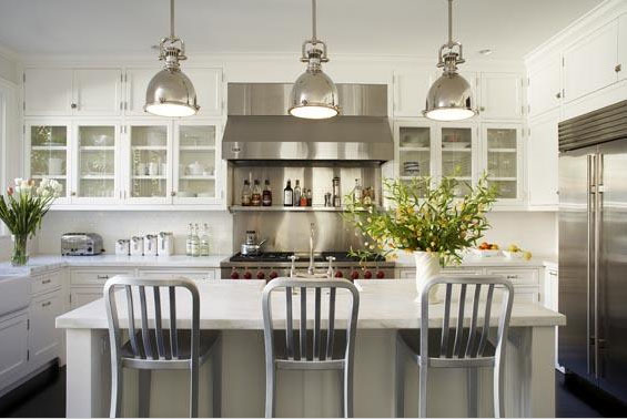 White kitchen with stainless steel appliances and pendant lights