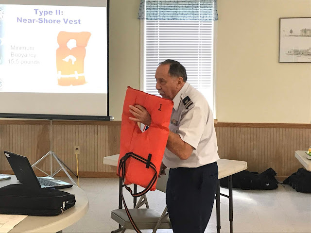 Auxiliarist Bill Castagno explains how the different types of life jackets work to save lives. Castagno is holding a type 2 vest which is meant for near shore use.