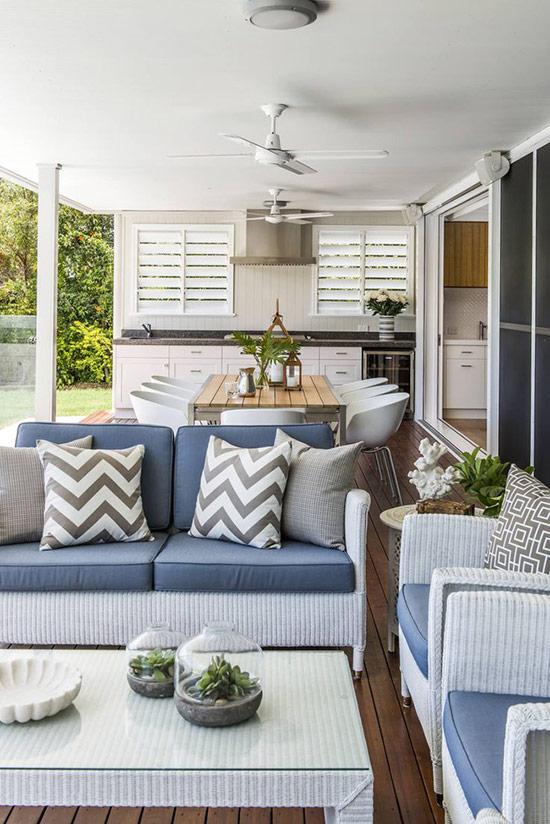 Phòng khách phong cách biển với nội thất bằng mây tre đan và phòng bếp với gam màu trắng cùng đảo bếp màu đen.