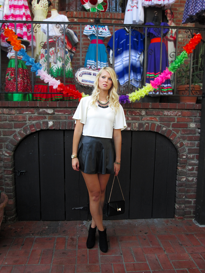 black leather skirt, white crop top, black wedge heels, bow tie clutch