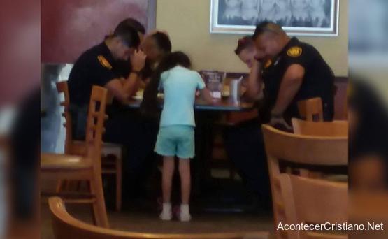 Niña orando por policías en un restaurante