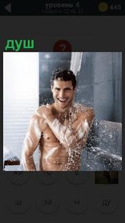 В ванной комнате мужчина принимает душ, после того как мылом все тело покрыл