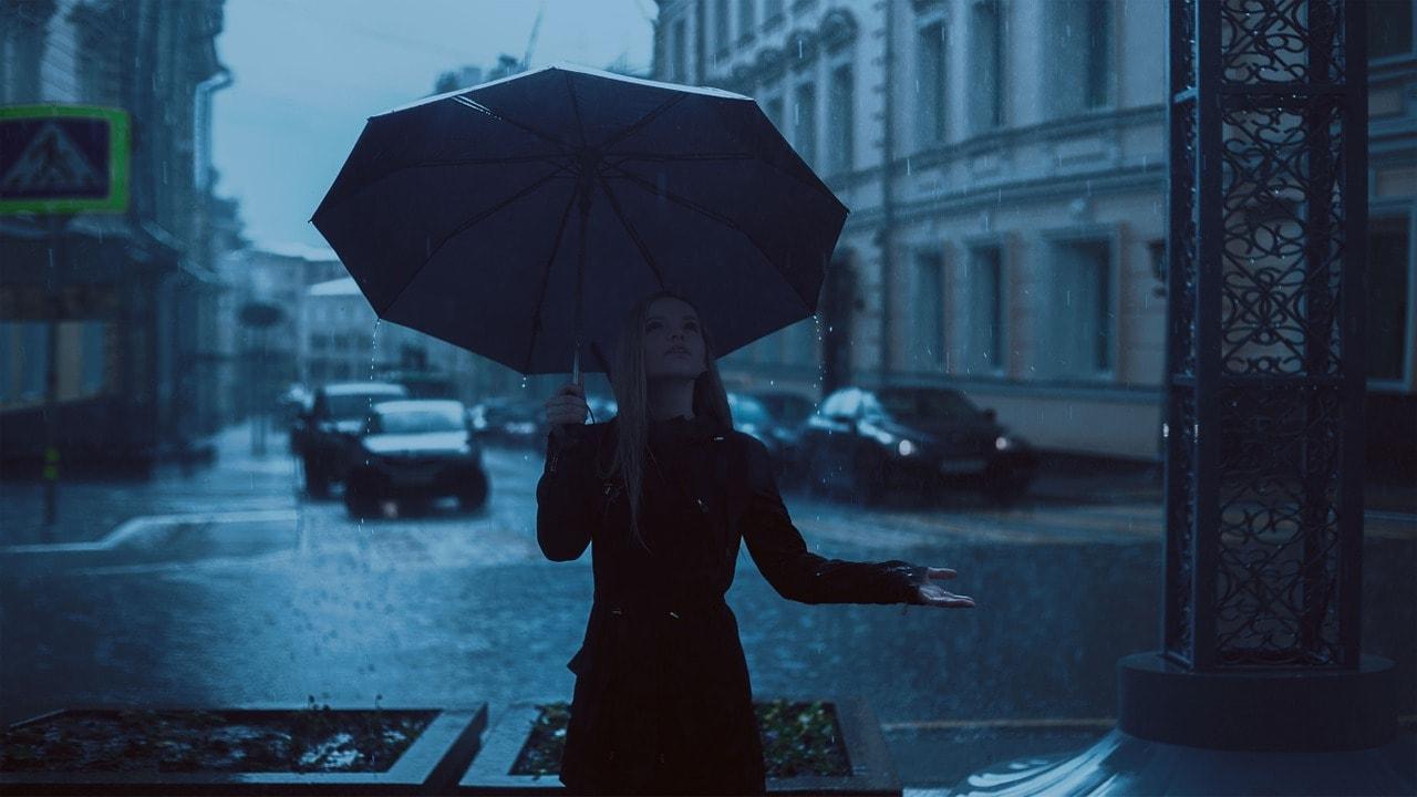 Chica bajo la lluvia con paraguas mirando a arriba