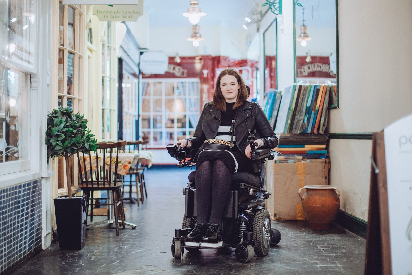 Shona is sitting in her powerchair, wearing a black midi dress with 3 white stripes and black and white flatform shoes, a leopard print bag rests on her lap. Shop fronts and tables and chairs can be seen to the left of her and behind her.