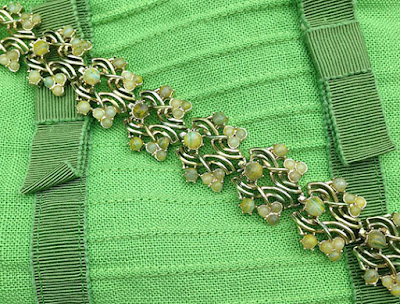 A midcentury bracelet lying across a green dress