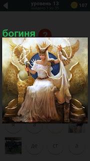 В большом красивом кресле сидит богиня и держит свои символы в руках