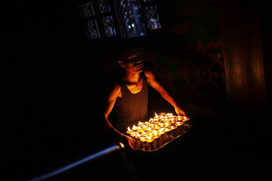 A man carries butter lamps lit by devotees at a monastery near the Boudhanath Stupa, an important pilgrimage site for Buddhists in Katmandu, Nepal, Wednesday, June 25, 2014.