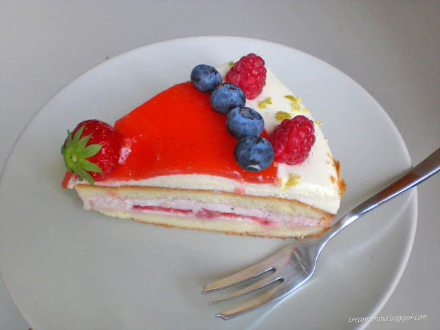 torta con mousse al cioccolato bianco topping di fragole e decorazione con frutti di bosco