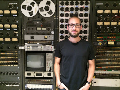 Image description: man posing in front of old-fashioned gray communications gear. There are analog meters, a tape-to-tape reel, a cathode-ray tube screen surrounded by switches, buttons, and dials. Directly behind the man is a plugboard with dozens of sockets.