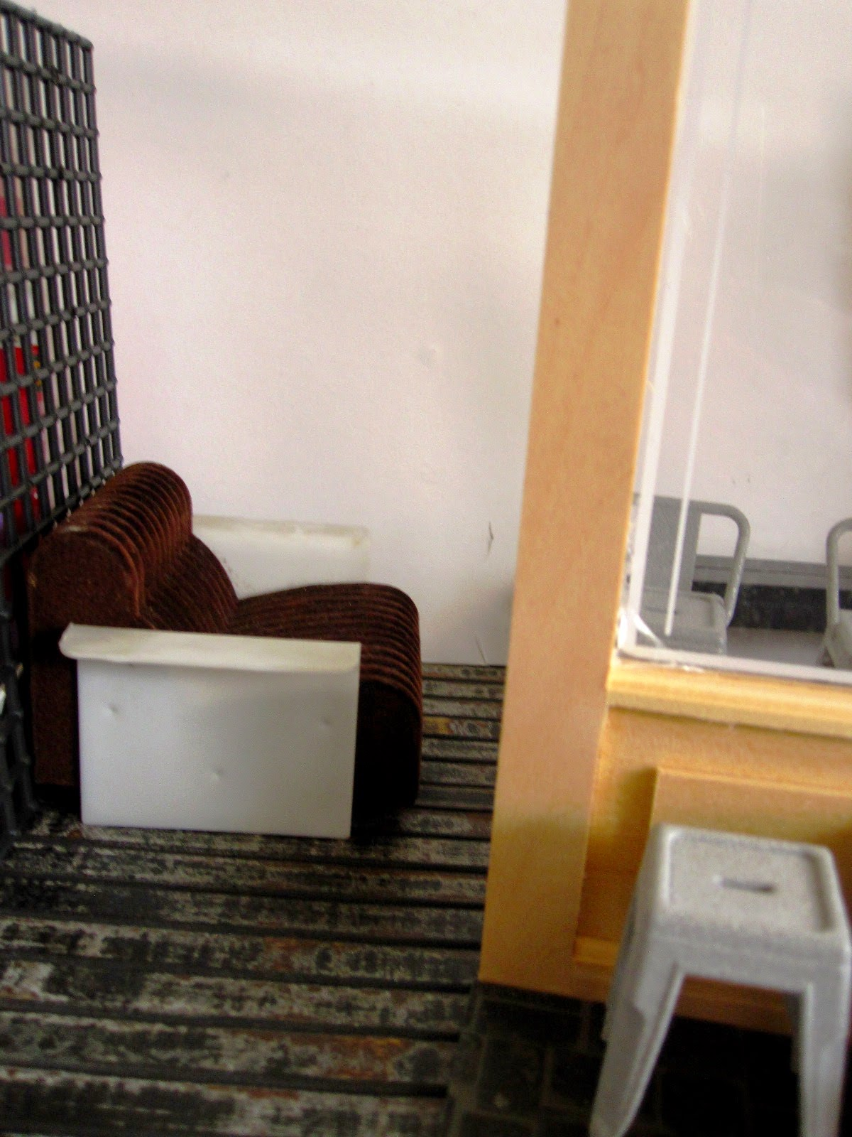 View through a mock up of the front of a modern dolls' house miniature cafe showing a lounge chair and several cafe chairs.