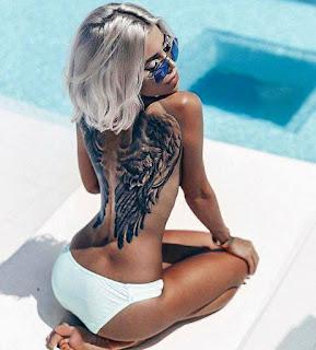 mujer rubia con tatuaje de alas
