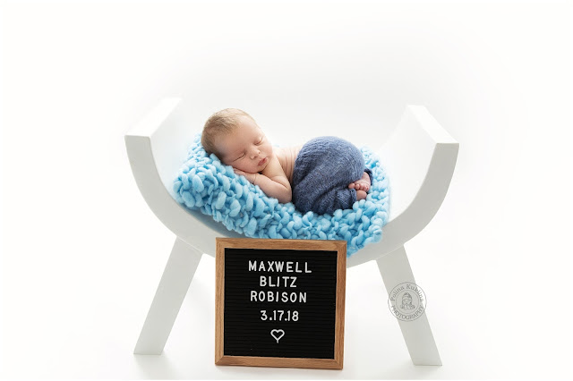 Sleeping baby on top of a blue blanket on a curved white bench with a square blackboard sign in front