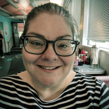 image of me from the shoulders up at a diner; I'm wearing a black and white striped top and grey-framed glasses, and my hair is pulled back into a ponytail