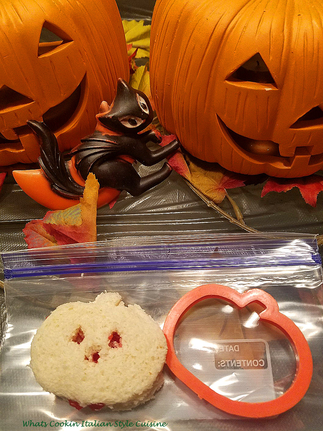A little sandwich made with cookie cutters for a halloween party, school lunches and more ideas using a pumpkin cookie cutter with soft bread and these have apricot jam in them